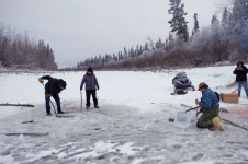 A long willow pole is run under the ice from the first hole to the second, trailing a rope behind.
